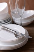 Set of white dishes on table on brown background — Stock Photo