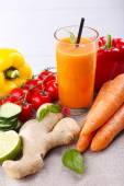 Glass of fresh carrot juice and vegetables on table cloth — Foto Stock