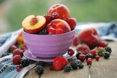 Peaches and berries in bowl on table close-up — Stock Photo