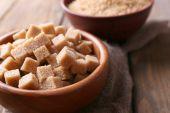 Brown sugar cubes and crystal sugar in bowl — Stock Photo