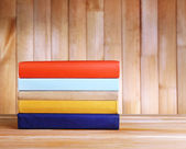 Books on wooden table on wooden wall background — Foto Stock