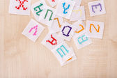 Handmade embroidered letters on white fabric, on wooden background — Stock Photo