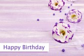 Beautiful artificial eustomas on purple wooden background — Stock Photo