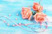 Beautiful roses on blue wooden background — Stock Photo
