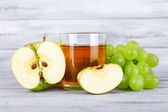 Glass of juice with fresh grape and apples on grey wooden table — Stock Photo
