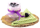 Healthy breakfast - yogurt with  blackberries and muesli served in glass jar, on wooden board, isolated on white — Stock Photo