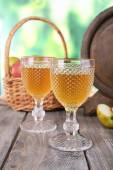 Still life with tasty apple cider and fresh apples, on nature background — Stock Photo