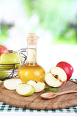 Apple cider vinegar in glass bottle and ripe fresh apples, on wooden table, on nature background — Stock Photo