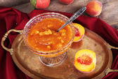 Tasty apricot jam with fresh apricots on wooden table — Stock Photo