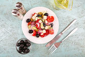 Greek salad and olive oil in plate on wooden background — Stock Photo