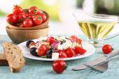 Greek salad in plate and bread on wooden table on natural background — Foto de Stock
