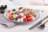 Greek salad served in plate on napkin on wooden table on natural background — Stock Photo