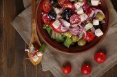 Greek salad served in brown bowl on sacking napkin on wooden background — Stock Photo
