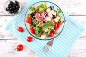 Glass bowl of Greek salad served on napkin on wooden background — Stock Photo