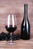 Tasty wine and ripe grape on wooden background — Stock Photo
