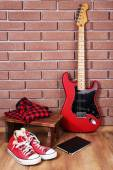 Guitar, trainers and clothes on brick wall background — Stock Photo