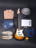 Musical equipment, clothes and footwear on dark background — Stock Photo