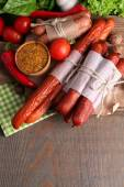 Assortment of thin sausages, mustard in bowl and spices on cutting board, on wooden background — Stock Photo