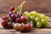Bunches of different kinds of grapes on wooden table on wooden wall background — ストック写真