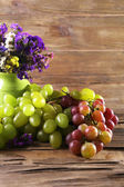 Bunches of ripe grapes and vase of fresh flowers on wooden table on wooden wall background — Stock Photo