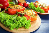 Stuffed red peppers with greens and vegetables on table close up — Stock Photo