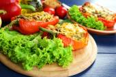 Stuffed red peppers with greens and vegetables on table close up — Foto de Stock