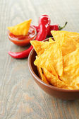 Tasty nachos, red tomatoes and chili pepper in color bowl on wooden background — Stok fotoğraf