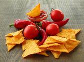 Lezzetli cips, kırmızı domates ve biber ahşap zemin üzerinde — Stok fotoğraf