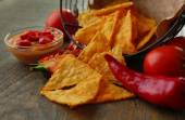 Tasty nachos, red tomatoes and chili pepper in basket on wooden background — Stock Photo