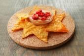 Lecker nachos und schüssel mit sauce an bord, auf hölzernen hintergrund — Stockfoto