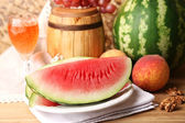 Composition of ripe watermelon, fruits, pink wine in glass and wooden barrel on  color wooden table, on color wall background — Foto Stock