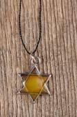Star David pendant on wooden background — Stock Photo