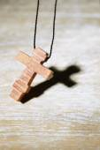Wooden cross with deep shadow on wooden background — Stock Photo