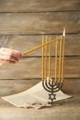 Hand burning candles on Menorah on wooden background — Foto de Stock