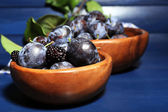 Ripe sweet plums in bowls, on wooden table — Foto Stock