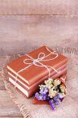 Livros e flores silvestres no guardanapo na mesa de madeira no fundo da parede de madeira — Foto Stock