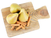 Ripe pears and cinnamon sticks on wooden cutting board, isolated on white — Stock Photo