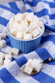 Refined sugar in color bowl on color napkin background — Stock Photo