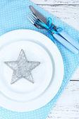White plates, fork, knife and Christmas decoration on blue polka dot napkin on wooden background — Stock Photo