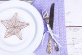 White plate, fork, knife and Christmas decoration on lilac polka dot napkin on wooden background — Stock Photo