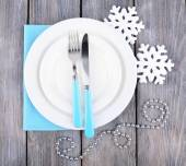 White plates, fork, knife and Christmas tree decoration on wooden background — Stock Photo