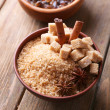 Brown sugar cubes and crystal sugar with spices in bowl on wooden background — Stock Photo #52843433