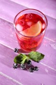 Glass of cold berry cocktail on wooden background — Stock Photo