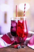 Glasses of cold berry cocktail and napkin on wooden table — Stock Photo