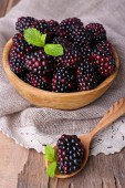 Wooden bowl of blueberries on sacking napkin on wooden background closeup — Stock Photo