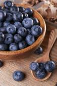 Wooden bowl of blueberries on cutting board on sacking napkin closeup — Stock Photo