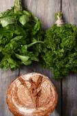 Fresh baked bread and fresh herbs, on wooden background — Foto Stock