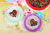 Delicious rainbow cakes on plates, on bright background — Stock Photo