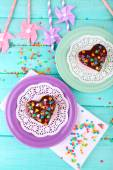 Delicious rainbow cakes on plates, on color wooden background — Stock Photo