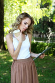 Beautiful young girl with tablet on city street — Stock Photo